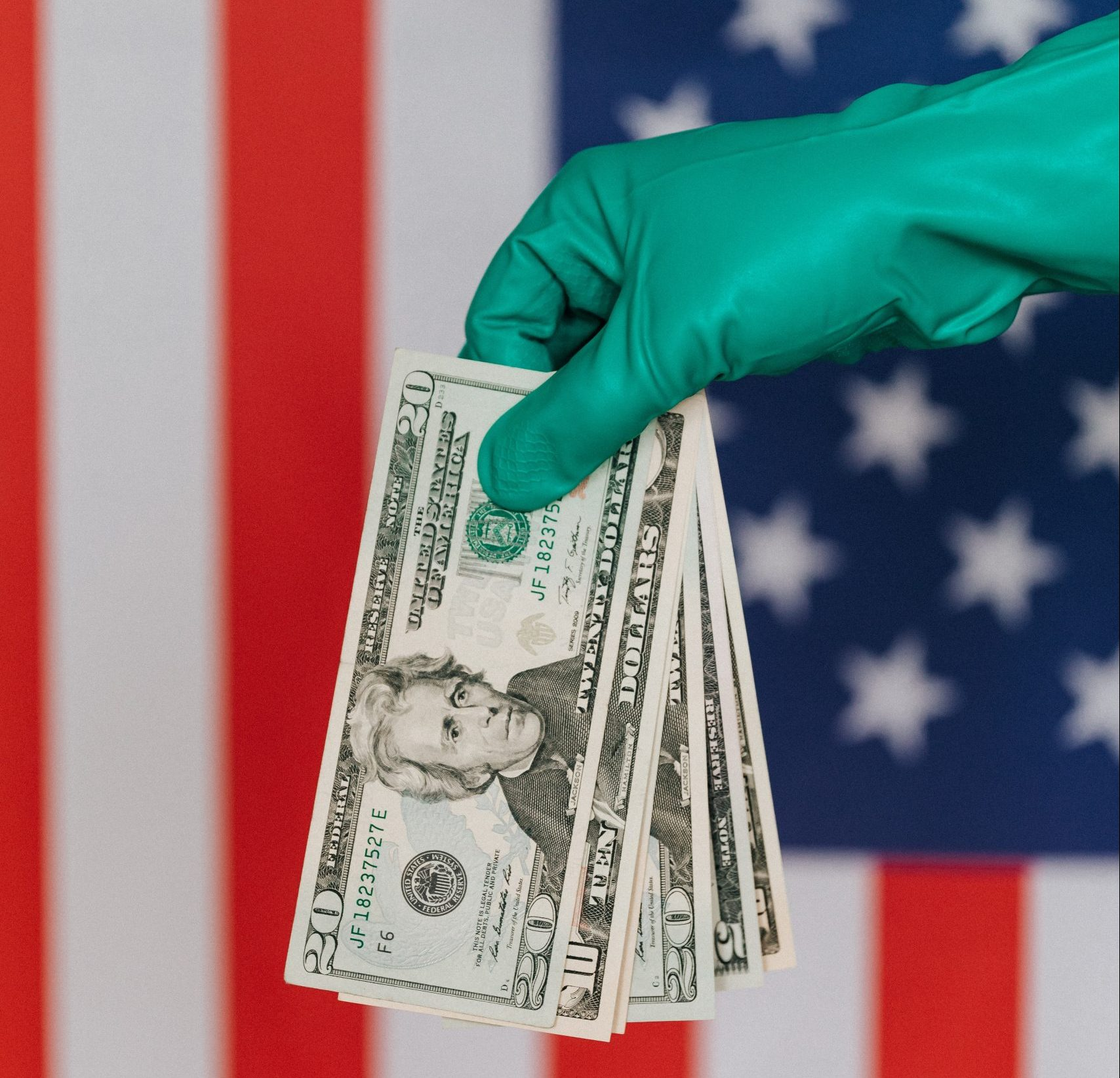crop-person-in-latex-gloves-with-american-money-on-background-of-flag